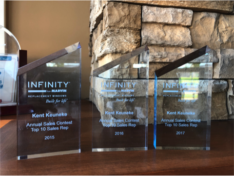 Photo of multiple Infinity awards received by a Bushey's staff member